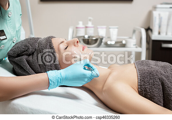 beautician applies face mask with brush to beautiful young woman in Spa salon. cosmetic procedure skin care. - csp46335260