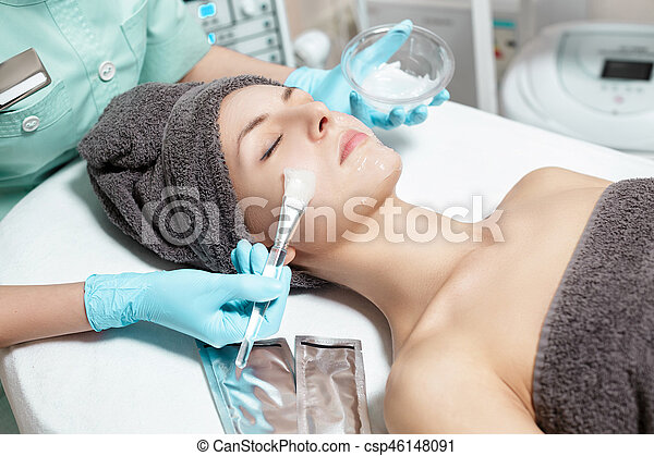 beautician applies face mask with brush to beautiful young woman in Spa salon. cosmetic procedure skin care. - csp46148091
