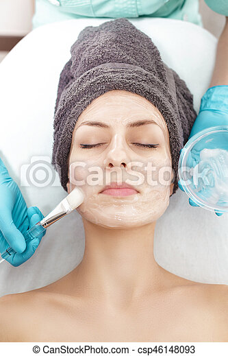 beautician applies face mask with brush to beautiful young woman in Spa salon. cosmetic procedure skin care. - csp46148093