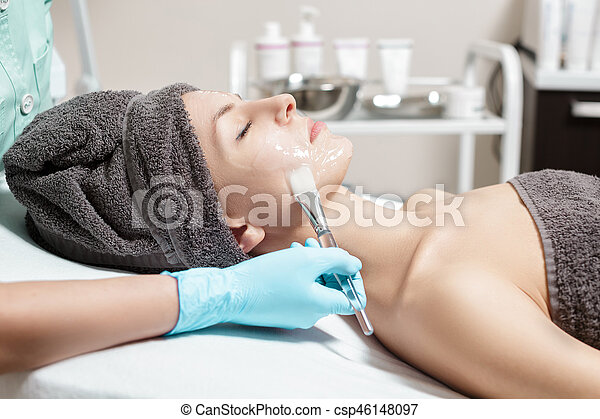 beautician applies face mask with brush to beautiful young woman in Spa salon. cosmetic procedure skin care. - csp46148097