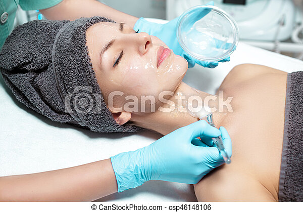beautician applies face mask with brush to beautiful young woman in Spa salon. cosmetic procedure skin care. - csp46148106