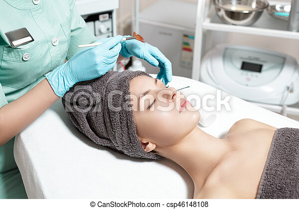 beautician applies face mask with brush to beautiful young woman in Spa salon. cosmetic procedure skin care. - csp46148108