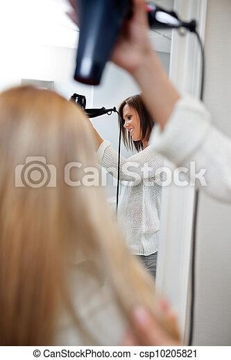 Beautician Blow Drying Hair Of Female Customer - csp10205821