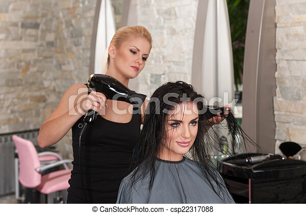 Beautician blow drying woman's hair after giving new haircut at parlor. blond girl drying dark-haired girl hair - csp22317088