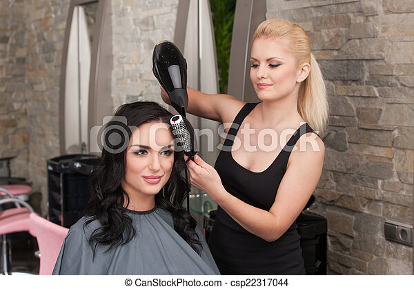Beautician blow drying woman's hair after giving new haircut at parlor. blond girl drying dark-haired girl hair and smiling - csp22317044