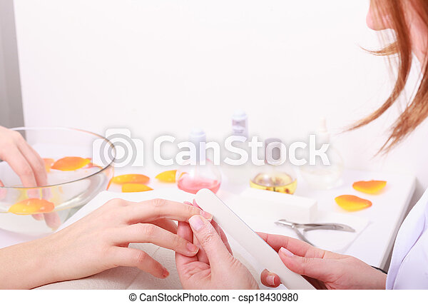 Beautician with file filing nails female client. Woman spa beauty salon - csp18430980