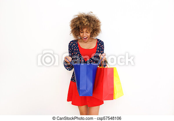 beautiful african american girl looking into shopping bag with surprised expression on face - csp57548106