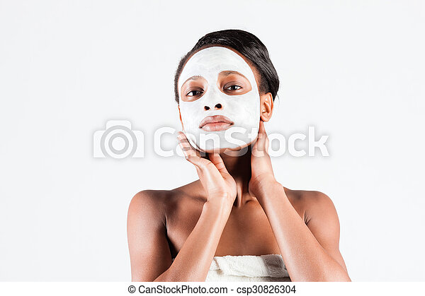 Beautiful African woman in Studio with facial mask - csp30826304