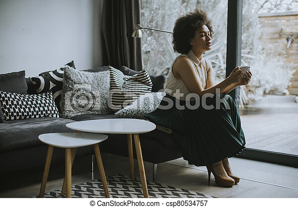 Beautiful afro american young woman with curly hair sitting by the window and holding a cup of coffee - csp80534757