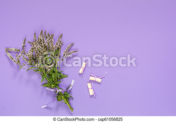 Beautiful amazing mint bouquet  with violet ribbon on violet surface. - csp61056825