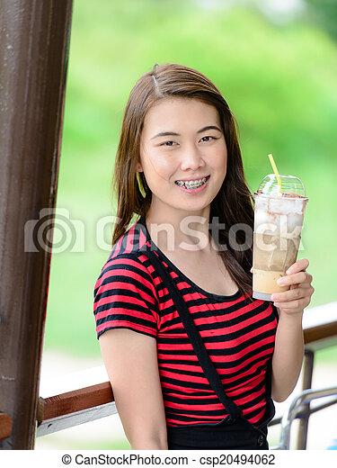 Beautiful Asian woman drinking coffee. - csp20494062