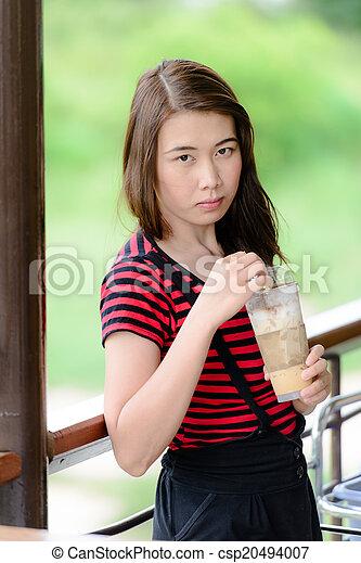Beautiful Asian woman drinking coffee. - csp20494007