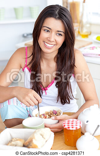 Beautiful asian woman having breakfast smiling at the camera sitting in the kitchen at home - csp4281371