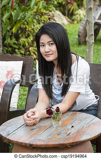 Beautiful Asian woman relax in park - csp19194964