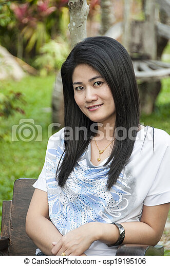 Beautiful Asian woman relax in park - csp19195106