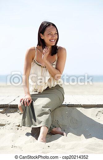 Beautiful asian woman smiling at the beach - csp20214352