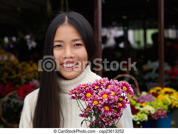 beautiful asian woman smiling with flowers - csp23613252