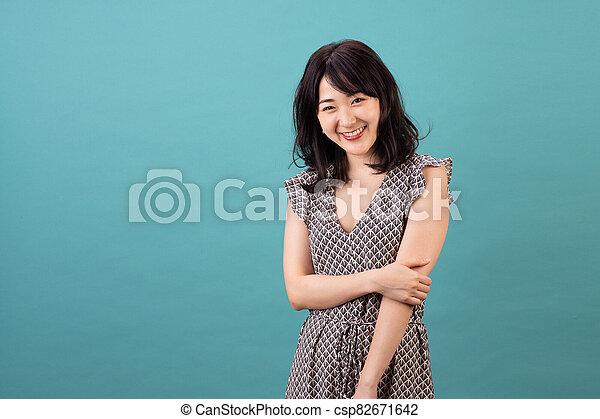 Beautiful asian woman wearing dress smiling - csp82671642