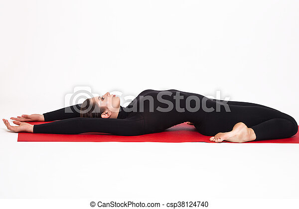 beautiful athletic girl in a black suit doing yoga supta