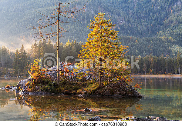 Beautiful autumn colors in the sunrise at the Hintersee lake in Bavaria alps - csp76310988