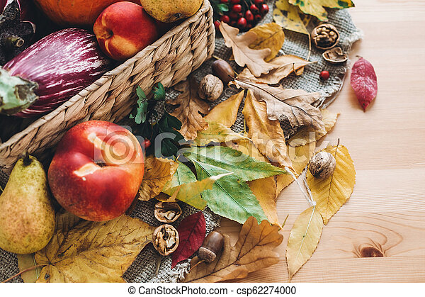 beautiful autumn pumpkin and vegetables in basket and colorful leaves with acorns and nuts on wooden table, top view. Fall bright image. Harvest time. Happy Thanksgiving - csp62274000