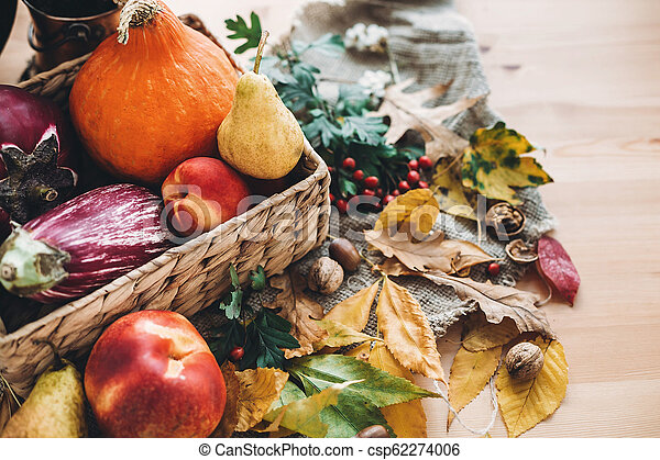 beautiful autumn pumpkin and vegetables in basket and colorful leaves with acorns and nuts on wooden table, top view. Fall bright image. Harvest time. Happy Thanksgiving - csp62274006