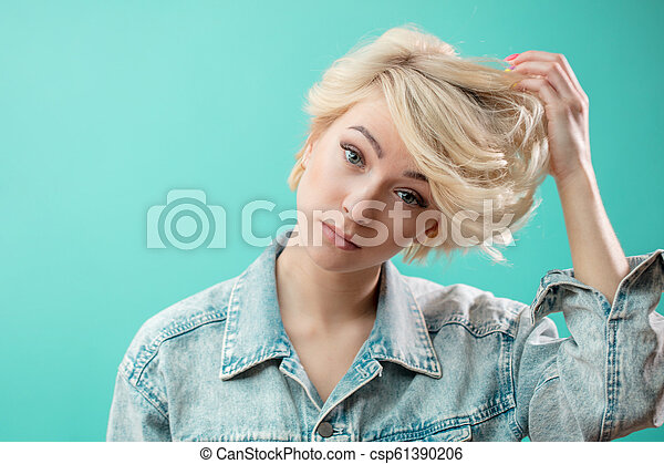 Beautiful awesome model with short blond hair looking at the camera - csp61390206