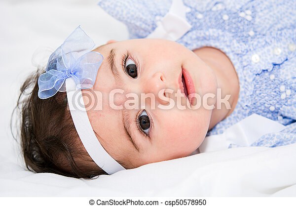 Beautiful baby girl on a bed - csp50578950