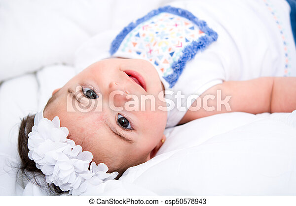 Beautiful baby girl on a bed - csp50578943