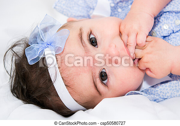 Beautiful baby girl on a bed - csp50580727