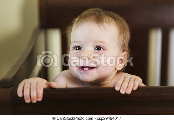 beautiful baby in a crib at home - csp29494017