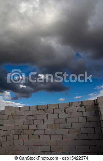 beautiful background of a brick wall and sky with clouds - csp15422374
