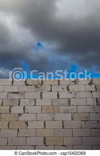 beautiful background of a brick wall and sky with clouds - csp15422369