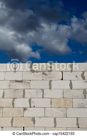 beautiful background of a brick wall and sky with clouds - csp15422193