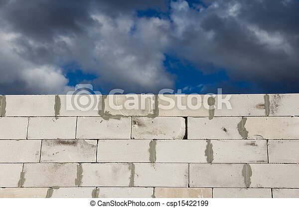 beautiful background of a brick wall and sky with clouds - csp15422199