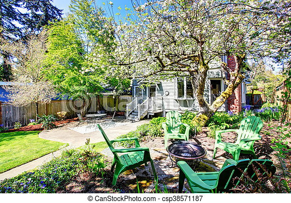 Beautiful backyard view with two patio areas and blooming trees. - csp38571187