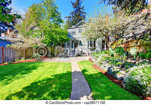 Beautiful backyard view with two patio areas and blooming trees. - csp38571192