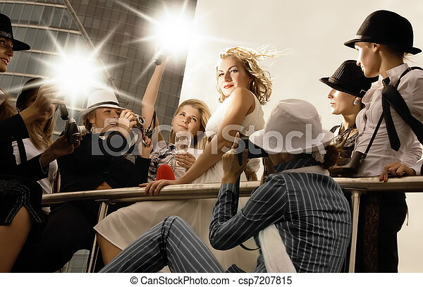 Beautiful blond girl looking like a superstar posing and lots of photographers around her taking pictures - csp7207815