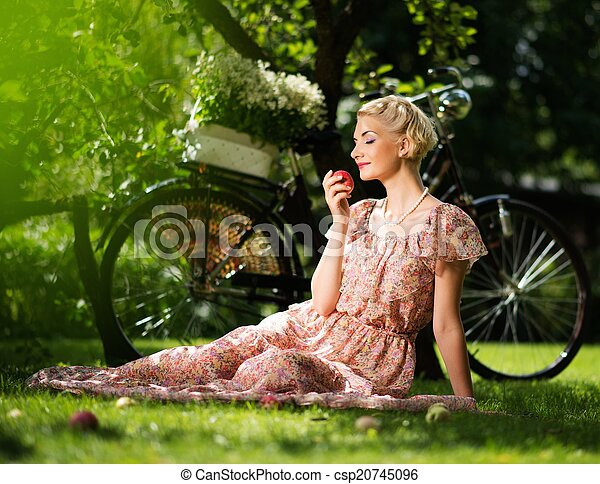 Beautiful blond retro woman with an apple and bicycle behind her - csp20745096