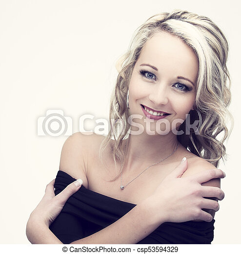Beautiful blond woman in curly hair and black top on light background - csp53594329