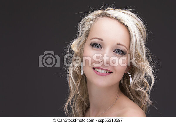 Beautiful blond woman in curly hair and black top on grey background - csp55318597
