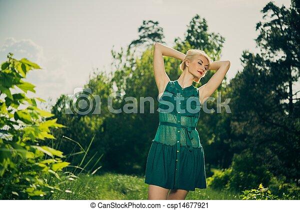 Beautiful blond woman in green dress outdoors - csp14677921