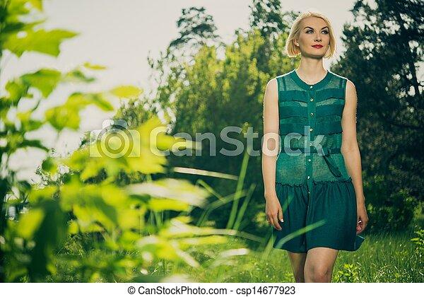 Beautiful blond woman in green dress outdoors - csp14677923