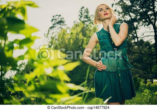 Beautiful blond woman in green dress outdoors - csp14677924