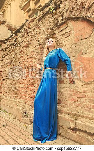Beautiful blond woman in long dress outdoors - csp15922777