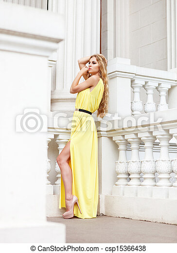 Beautiful blond woman in long dress outdoors - csp15366438