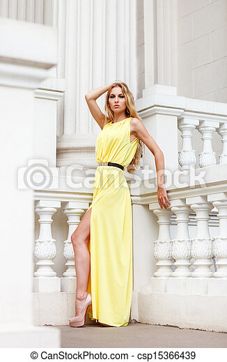 Beautiful blond woman in long dress outdoors - csp15366439