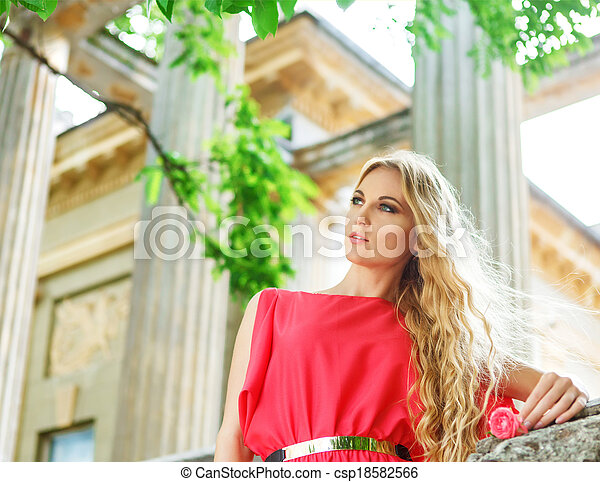 Beautiful blond woman in long red dress - csp18582566