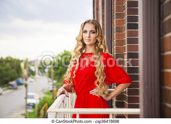Beautiful blond woman in red long dress - csp36418698