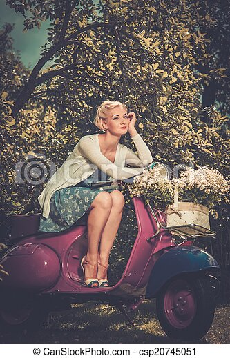Beautiful blond woman sitting on a retro roller  - csp20745051